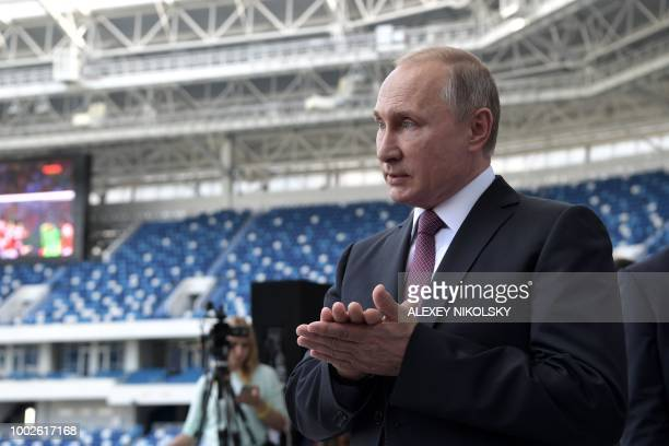 Russian President Vladimir Putin speaks and gestures as he visits the Kaliningrad Stadium during his working trip to Kaliningrad on July 20 2018