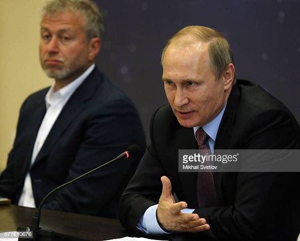 Russian President Vladimir Putin speaks as billionaire and businessman Roman Abramovich looks on during a meeting with top businessmen while visiting...