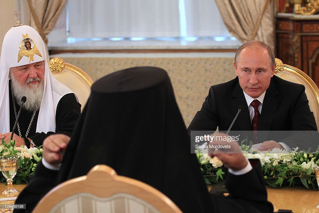 Russian President Vladimir Putin (R) speaks as Russian Orthodox Patriarch Kirill (L) looks on during a meeting with Orthodox Churches leaders in the Kremlin on July 25, 2013 in Moscow, Russia. Orthodox Patriarchs have traveled to Moscow to celebrate the 1025th anniversary of Christianity in Russia.