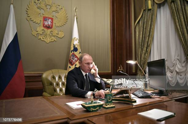 Russian President Vladimir Putin speaks on the phone in his office in Saint Petersburg on December 15 2018 with Artyom Palyanov a boy with brittle...