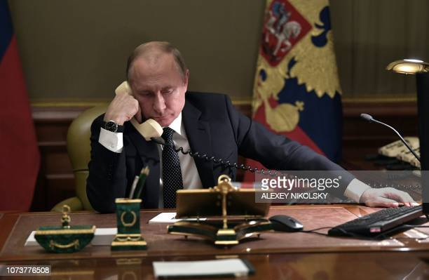 TOPSHOT Russian President Vladimir Putin speaks on the phone in his office in Saint Petersburg on December 15 2018 with Artyom Palyanov a boy with...