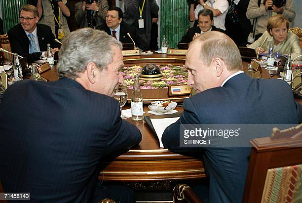 Russian President Vladimir Putin speaks to his US counterpart george W. Bush during a G8 leaders working session at Konstantinovsky Palace outside...