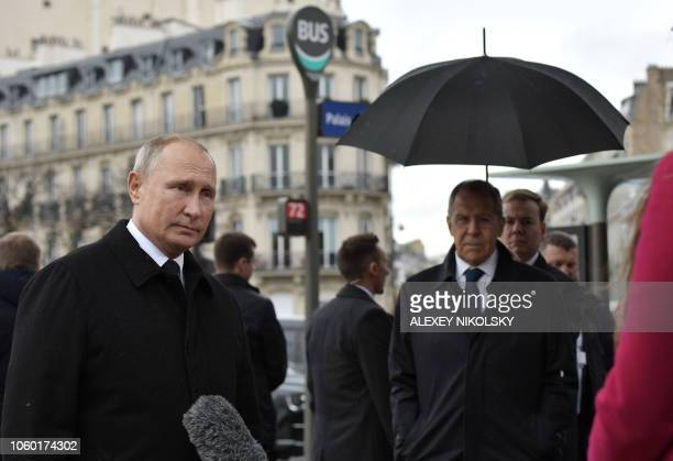 Russian President Vladimir Putin speaks to journalists as Russian Foreign Minister Sergei Lavrov looks on after the flowerlaying ceremony marking the...