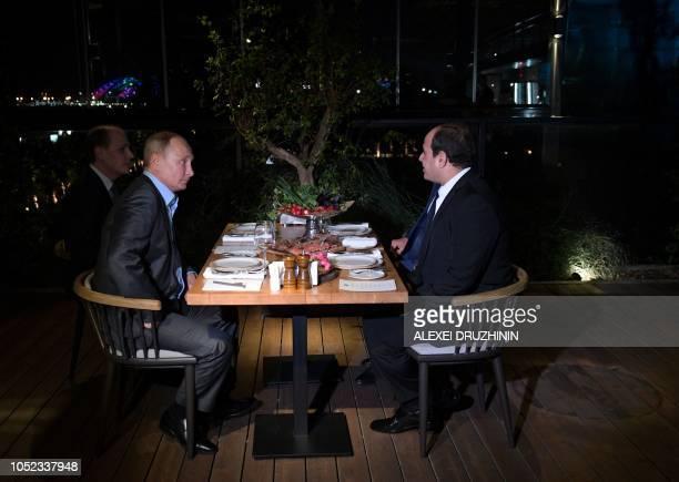 TOPSHOT Russian President Vladimir Putin speaks with Egyptian President Abdel Fattah AlSisi during their informal dinner in Sochi on October 16 2018