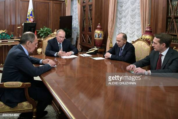 Russian President Vladimir Putin speaks with Foreign Minister Sergei Lavrov director of the Foreign Intelligence Service Sergei Naryshkin and...