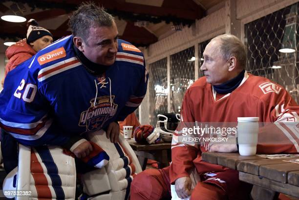 Russian President Vladimir Putin speaks with Governor of the Tula Region Alexei Dyumin during a ten minutes' break during the Night Hockey League...