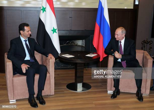 Russian President Vladimir Putin speaks with his Syrian counterpart Bashar alAssad during their meeting in Sochi on May 17 2018