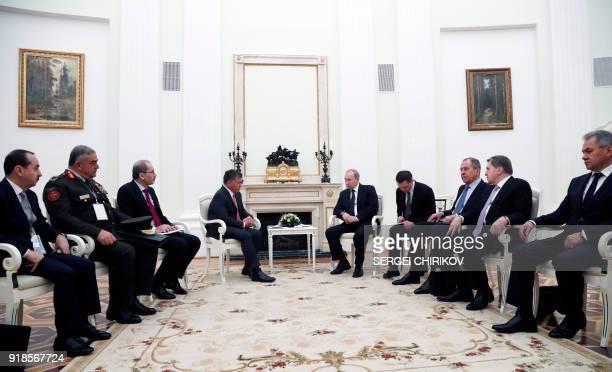 Russian President Vladimir Putin speaks with King Abdullah II of Jordan as members of their delegations look on during their meeting at the Kremlin...