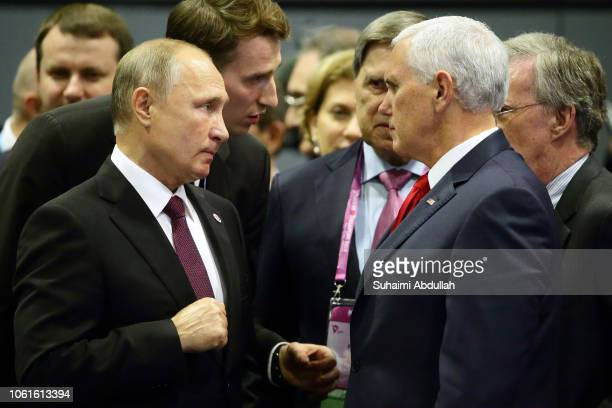 Russian President Vladimir Putin speaks with US Vice President Mike Pence at the 13th East Asia summit plenary session on the sidelines of the 33rd...