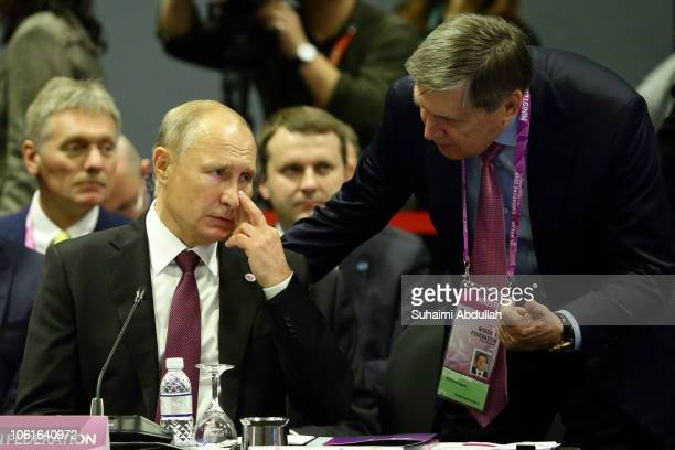 Russian President Vladimir Putin speaks with Yuri Ushakov at the 13th East Asia summit plenary session on the sidelines of the 33rd Association of...