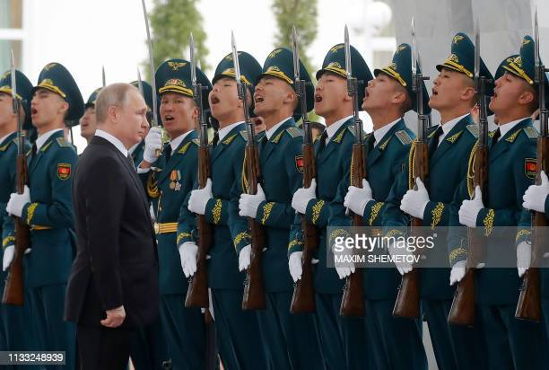 Russian President Vladimir Putin stands in front of guards of honour during a welcoming ceremony ahead of the talks with his Kyrgyz counterpart in...