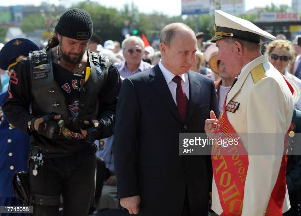 Russian President Vladimir Putin stands next to Russian Bikers' Association president Alexander Zaldostanov as he speaks with WWII veterans after the...