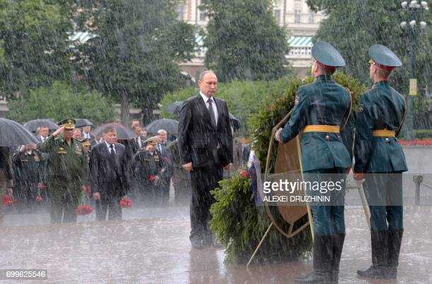 TOPSHOT Russian President Vladimir Putin stands under pouring rain during a wreathlaying ceremony marking the 76th anniversary of the Nazi German...