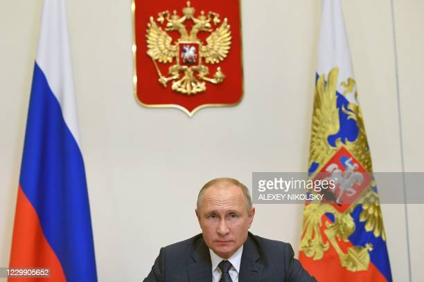 Russian President Vladimir Putin takes part in the opening of multi-purpose medical centers of the Russian Defence Ministry via a video link at the...