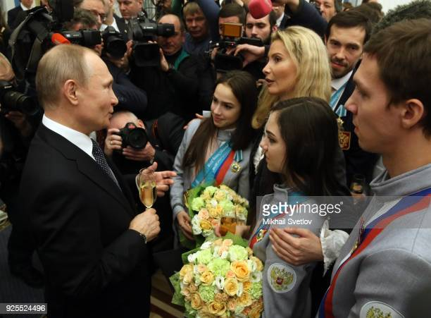 Russian President Vladimir Putin talks to figure skaters Alina Zagitova Evgenia Medvedeva and their coach Eteri Tutberidze during his meeting with...