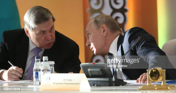 Russian President Vladimir Putin talks to his aide Yuri Ushakov during the 15th Forum of Interregional Cooperation of Russia and Kazakhstan on...