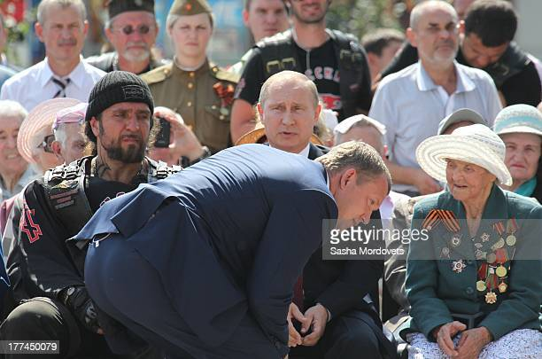 Russian President Vladimir Putin talks to his bodyguard Night Wolves Moscow Bikers club leader Alexander 'Khirurg' Zaldostanov looks on at the...