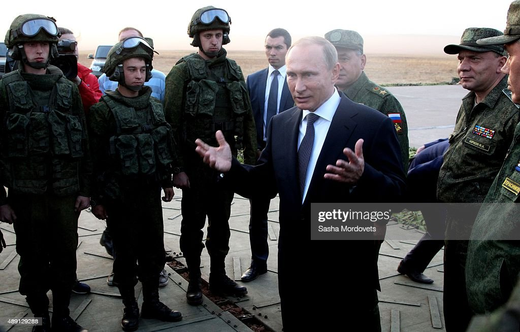 Russian President Vladimir Putin talks to officers as he attends Russias large-scale Center-2015 military exercises at Donguzsky Range September 19, 2015 in Orenburg, Russia, The exercises, aim to contain the outbreak of an armed conflict in Central Asia. Putin said this week that it's impossible to defeat Islamic State group without support of the government of Syria and that Moscow has provided military assistance to President Bashar al-Assad's regime and will continue to do so.