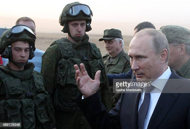 Russian President Vladimir Putin talks to officers as he attends Russias large-scale Center-2015 military exercises at Donguzsky Range September 19,...
