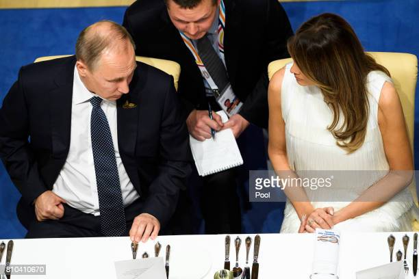 Russian President Vladimir Putin talks to the US first lady Melania Trump as they attend a state banquet in the Elbphilarmonie concert Hall on the...