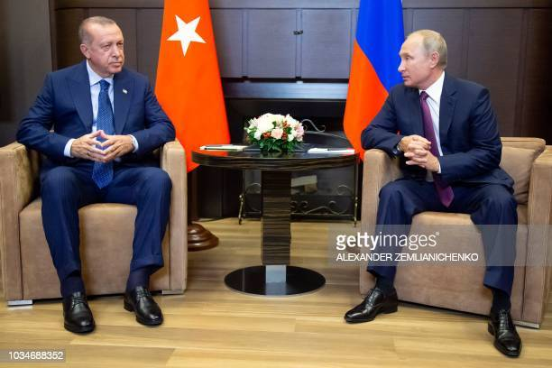 Russian President Vladimir Putin talks to Turkish President Recep Tayyip Erdogan during their meeting in the Bocharov Ruchei residence in the Black...