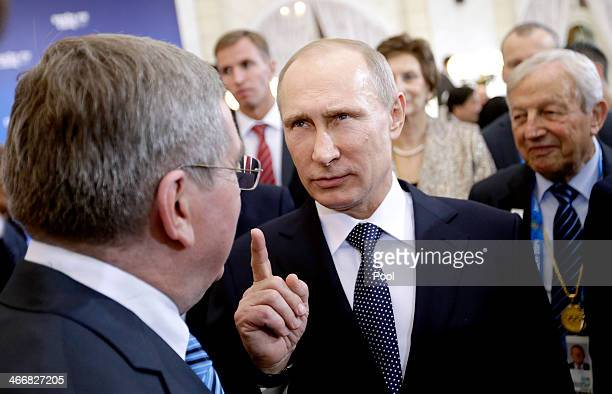 Russian President Vladimir Putin talks with International Olympic Committee President Thomas Bach at a welcoming event for IOC members ahead of the...