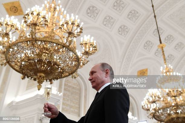 TOPSHOT Russian President Vladimir Putin toasts with attendees after a ceremony to bestow state awards on military personnel who fought in Syria at...