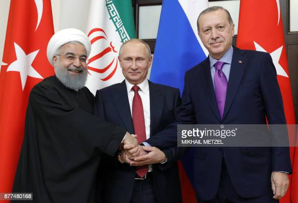 TOPSHOT Russian President Vladimir Putin Turkish President Recep Tayyip Erdogan and Iranian President Hassan Rouhani pose during a trilateral meeting...
