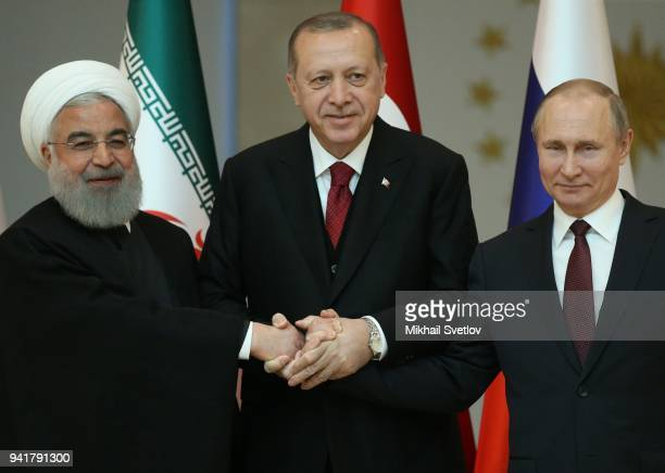 Russian President Vladimir Putin Turkish President Recep Tayyip Erdogan and Iranian President Hassan Rouhani hold hands as they pose for a photo...