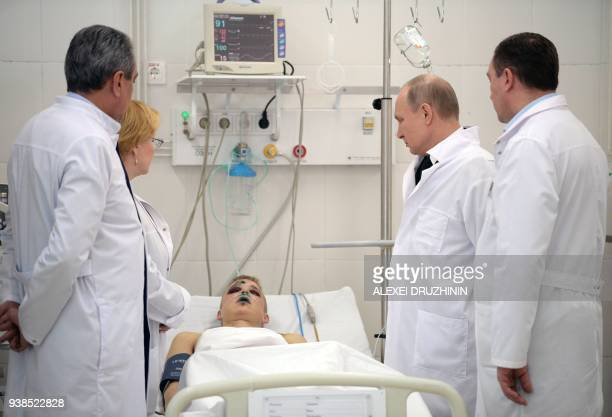 TOPSHOT Russian President Vladimir Putin visits people injured in a fire at a shopping centre at a hospital in Kemerovo on March 27 2018 Russian...