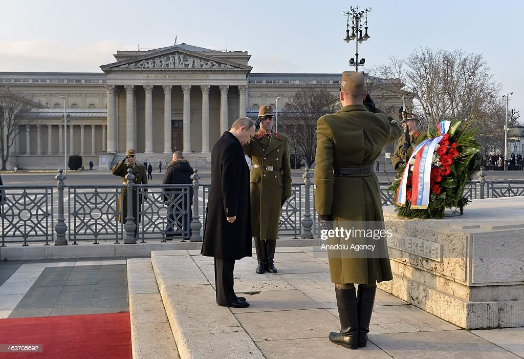 Russian President Vladimir Putin (C) visits the Memorial Stone of Heroes in the Heroes' Square in Budapest, Hungary on February 17, 2015.