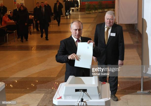 Russian President Vladimir Putin votes with his ballot at the polling station on March 18 2018 in Moscow Russia Russians are going to polls today in...