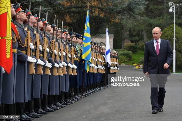 TOPSHOT Russian President Vladimir Putin walks past honour guards as he attends the unveiling ceremony of a monument to Tsar Alexander III the father...