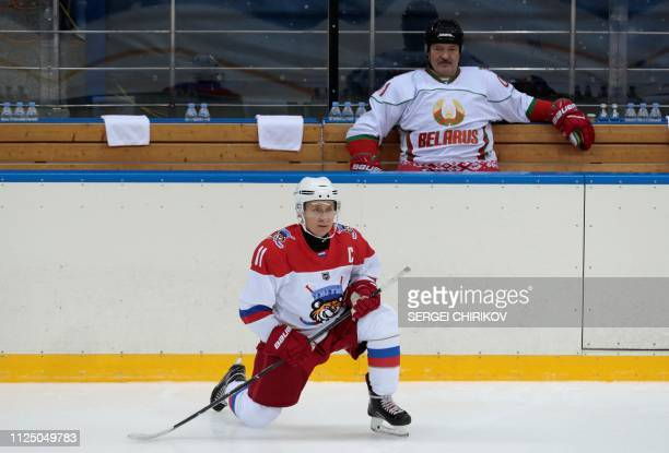 Russian President Vladimir Putin warms up as Belarus President Alexander Lukashenko looks on before playing an ice hockey game at Shayba Arena in the...