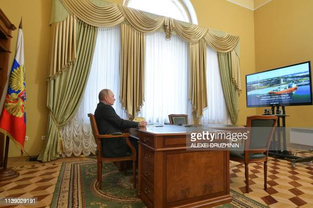 TOPSHOT Russian President Vladimir Putin watches a live broadcast of the ceremony to load the liquefied natural gas tanker Coral Anthelia at the...
