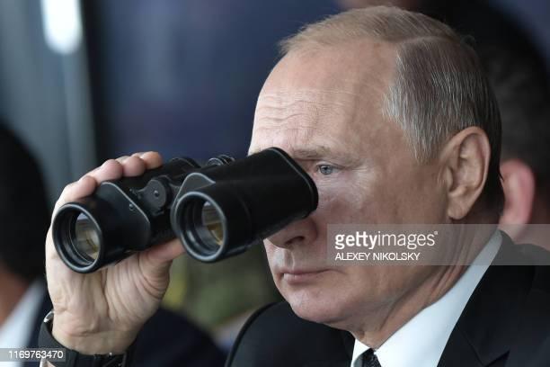 Russian President Vladimir Putin watches with binoculars the Tsentr-2019 military exercise at the Donguz range near Orenburg city on September 20,...