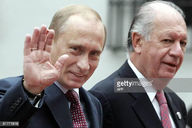 Russian President Vladimir Putin waves as Chilean President Ricardo Lagos accompanies him at the La Moneda Palace in Santiago Chile 21 November 2004...