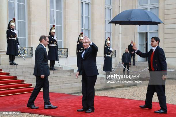 Russian President Vladimir Putin waves as he arrives to attend a lunch at the Elysee Palace in Paris on November 11 2018 during commemorations...
