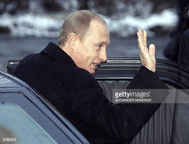 Russian President Vladimir Putin waves as he leaves a polling station where he voted in a parliamentary election in Moscow 07 December 2003 Putin...