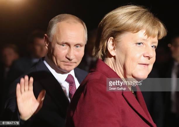 Russian President Vladimir Putin waves as he walks with German Chancellor Angela Merkel upon his arrival to discuss the Ukrainian peace process at...