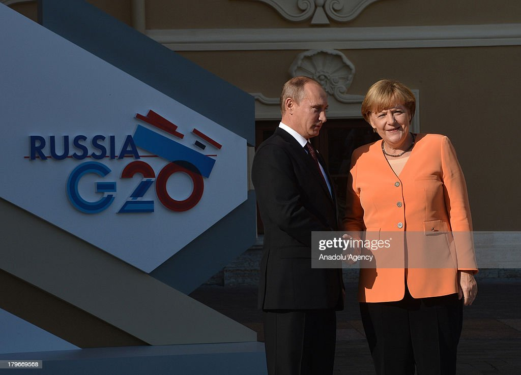 Russian President Vladimir Putin welcomes German Chancellor Angela Merkel (R) during arrivals for the G-20 summit at the Konstantin Palace in St. Petersburg, Russia on September 5,2013. The G20 summit begins on September 5, 2013 in Strelna of Saint Petersburg under Russian Presidency.