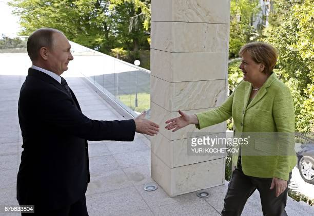 Russian President Vladimir Putin welcomes German Chancellor Angela Merkel during their meeting at the Bocharov Ruchei state residence in Sochi on May...