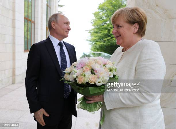 Russian President Vladimir Putin welcomes German Chancellor Angela Merkel during their meeting in Sochi on May 18 2018