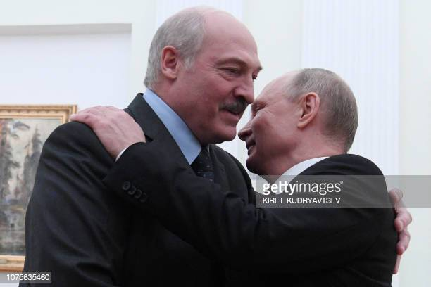 Russian President Vladimir Putin welcomes his Belarus counterpart Alexander Lukashenko during their meeting at the Kremlin in Moscow on December 29...