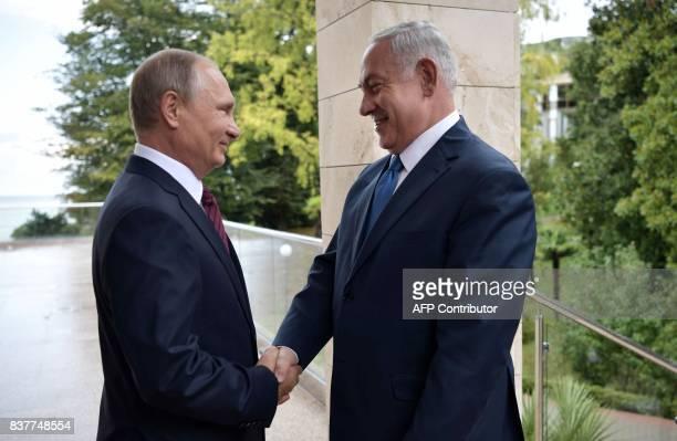 TOPSHOT Russian President Vladimir Putin welcomes Israeli Prime Minister Benjamin Netanyahu during a meeting at the Bocharov Ruchei state residence...