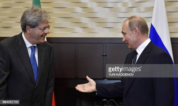 Russian President Vladimir Putin welcomes Italian Prime Minister Paolo Gentiloni during a meeting at the Bocharov Ruchei state residence in Sochi on...
