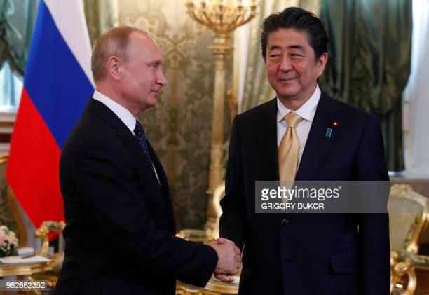 Russian President Vladimir Putin welcomes Japanese Prime Minister Shinzo Abe at the Kremlin in Moscow on May 26 2018