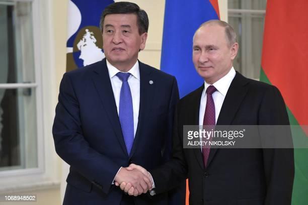 Russian President Vladimir Putin welcomes Kyrgyz President Sooronbay Jeenbekov prior to a meeting of the Supreme Eurasian Economic Council in Saint...