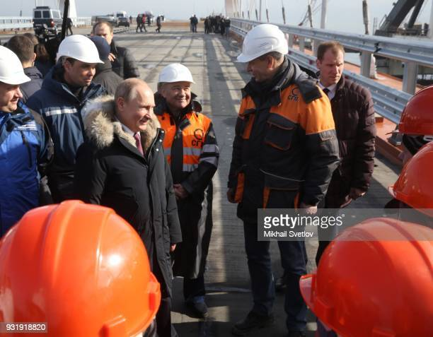 Russian President Vladimir Putin with workers during a visit the construction site for the Crimean bridge which is being built to connect the...