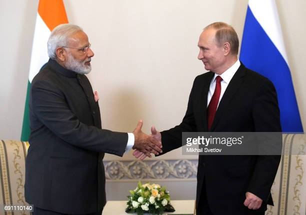 Russian President Vladmir Putin greets Indian Prime Minister Narendra Modi during their meeting at the Konstantin Palace during the International...